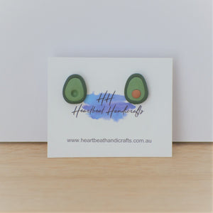 Studio shot of Heartbeat Handicrafts avocado studs on timber and white background