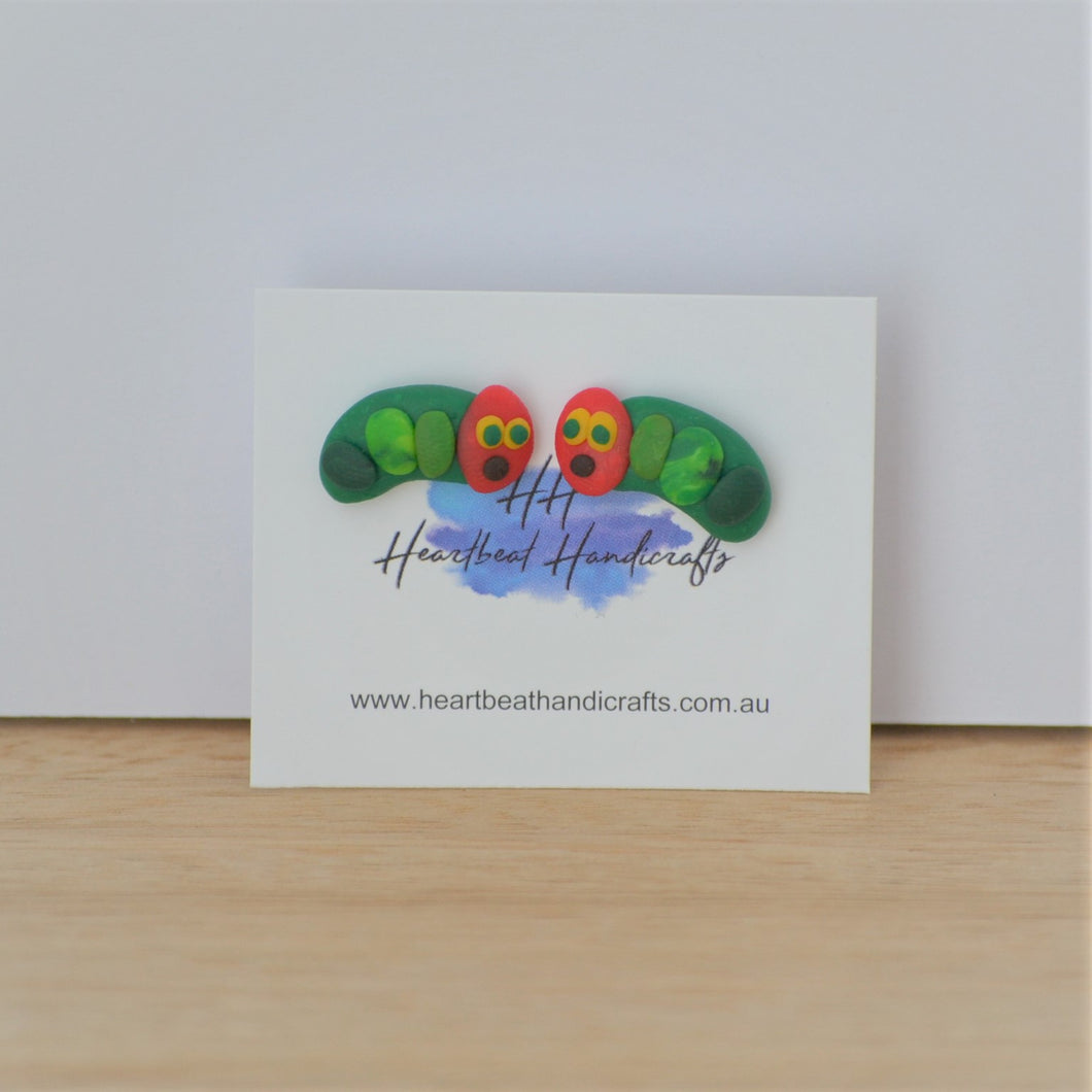 Caterpillar stud earrings shown on earrings card on timber and white background