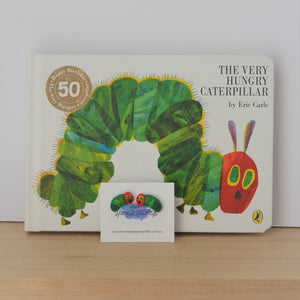 Caterpillar stud earrings shown in front of The Very Hungry Caterpillar book