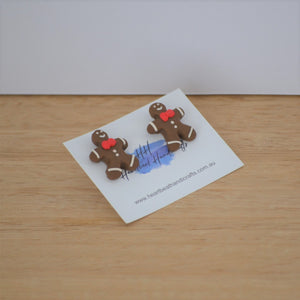 Christmas gingerbread stud earrings angled on backing card on timber background