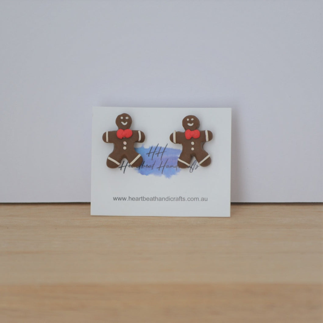 Christmas gingerbread stud earrings on backing card on timber background