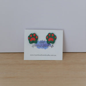 Christmas pawprint stud earrings on backing card on timber background