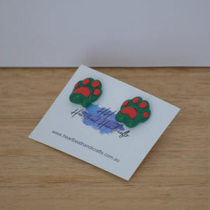 Christmas pawprint stud earrings up close on backing card on timber background