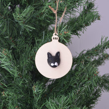 Bauble shaped christmas ornament with a handmade polymer clay cat face attached, hanging in a christmas tree.