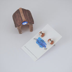 custom dog cufflinks shiwn on display card beside clay miniature kennel