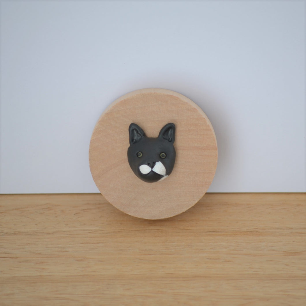 Bottle opener with custom black cat face sculpture attached