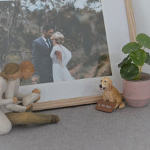 Handmade Golden retriever dog figurine beside a photo frame
