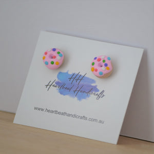 Pink donut stud earrings shown angled on earrings card on timber and white background