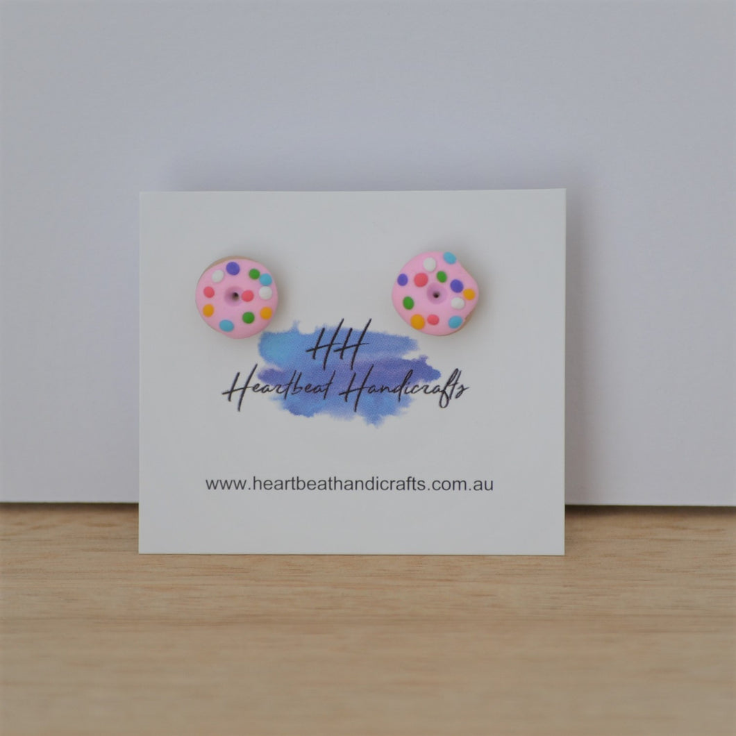 Pink donut stud earrings shown on earrings card on timber and white background