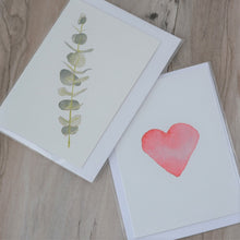 Two watercolour print greeting cards overlapping on a timber flooring background