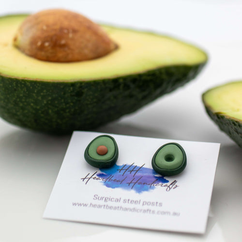 Avocado stud earrings on card shown in front of actual cut avocado