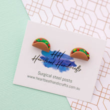 Taco stud earrings shown on earrings card on paper background