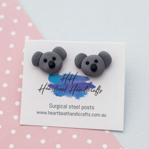 Koala stud earrings shown on earrings card on paper background