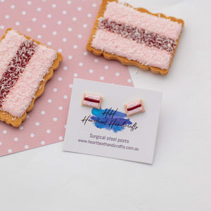 Iced vovo stud earrings shown on earrings card shown in front of actual biscuits