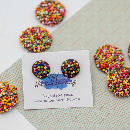 Chocolate freckle stud earrings shown on earrings card on paper surrounded by freckles
