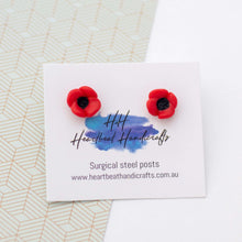 Poppy stud earrings shown on earrings card on patterned and white background