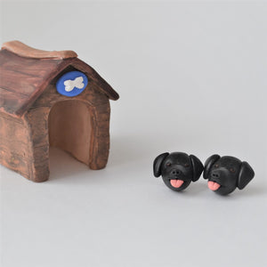 Handmade polymer clay black lab stud earrings shown styled beside mini kennel