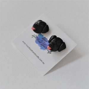 Handmade polymer clay black lab stud earrings shown on earring card
