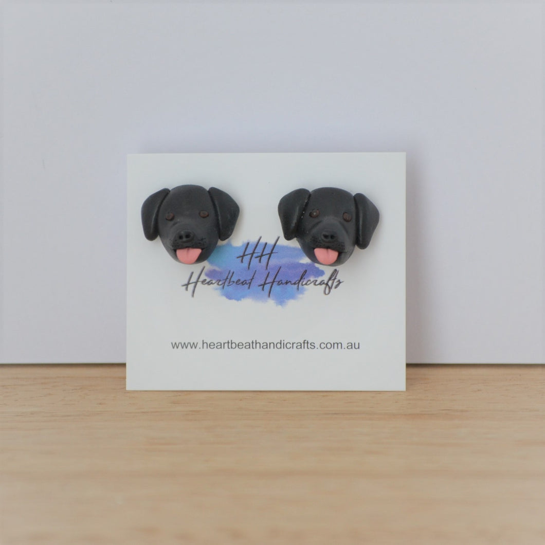 Handmade polymer clay black lab stud earrings shown on timber