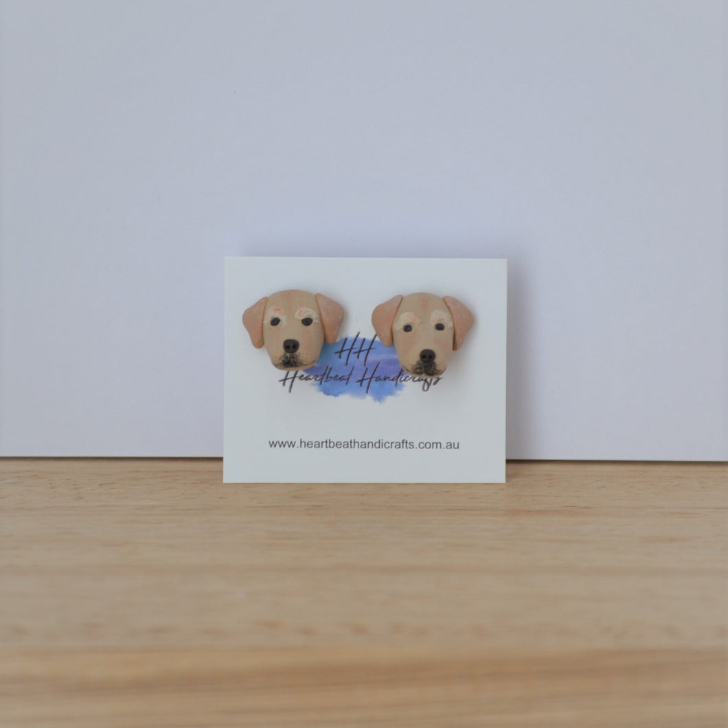 Handmade polymer clay golden lab retriever stud earrings shown on timber