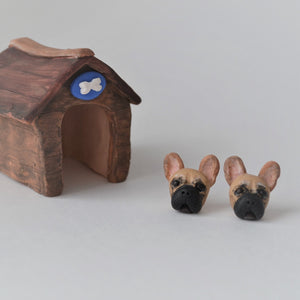 Handmade polymer clay french bulldog stud earrings shown beside mini kennel