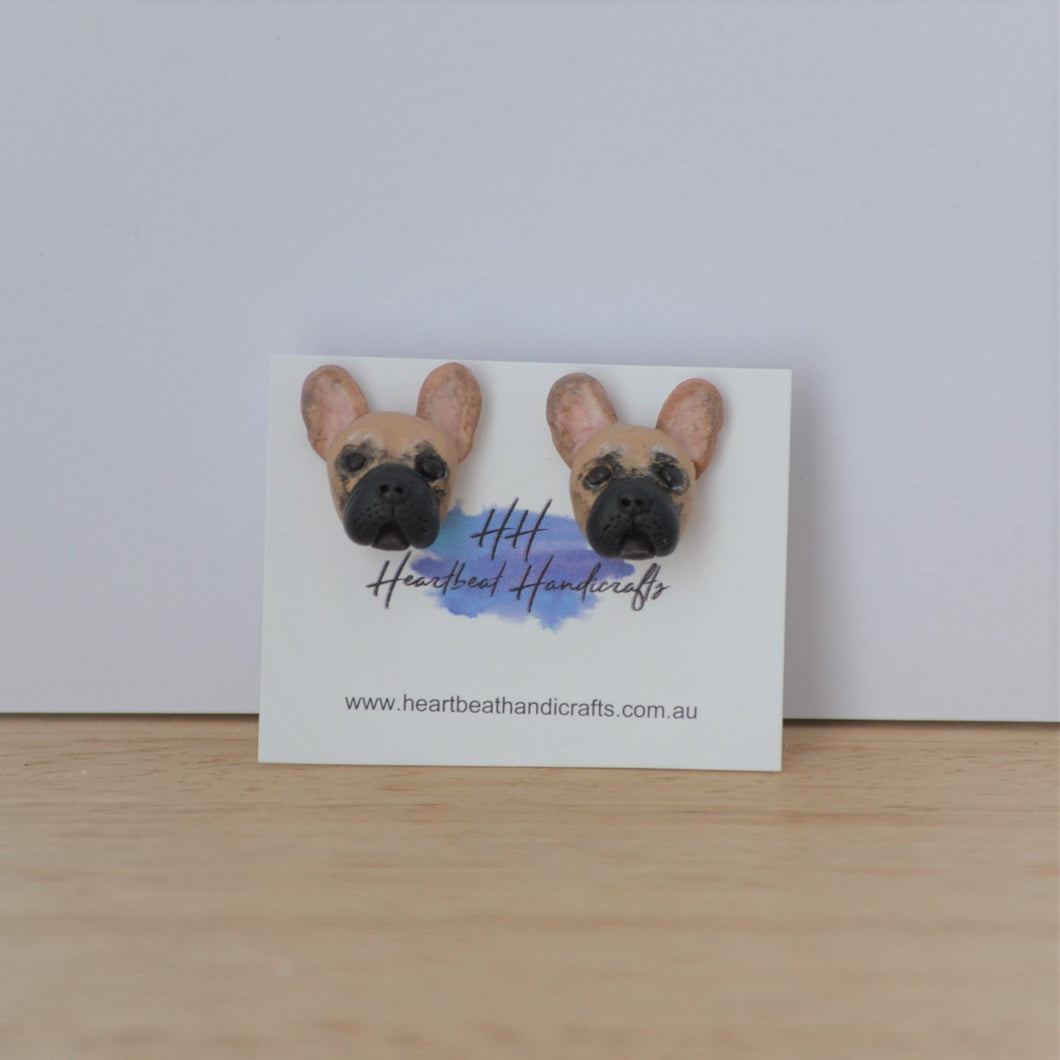 Handmade polymer clay french bulldog stud earrings shown on timber