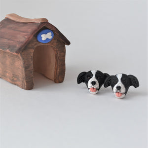 Handmade polymer clay border collie stud earrings shown beside mini kennel