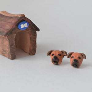 Handmade polymer clay Staffy stud earrings shown styled beside mini kennel