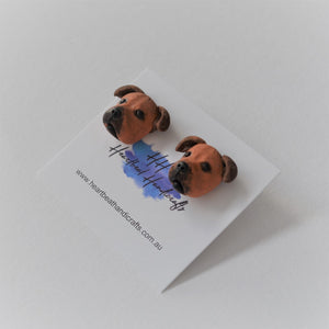 Handmade polymer clay Staffy stud earrings shown close up