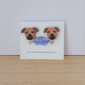 Handmade polymer clay Staffy stud earrings shown on timber