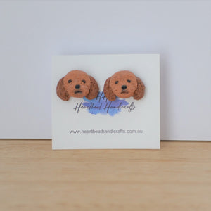 Handmade polymer clay Cavoodle stud earrings shown on timber