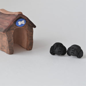 Handmade polymer clay black poodle stud earrings shown beside mini kennel