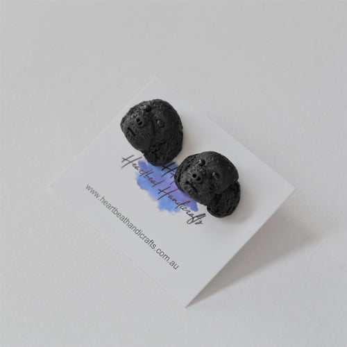 Handmade polymer clay black poodle stud earrings shown close up
