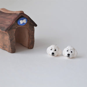 Handmade polymer clay white poodle stud earrings shown beside kennel