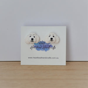 Handmade polymer clay white poodle stud earrings shown on timber