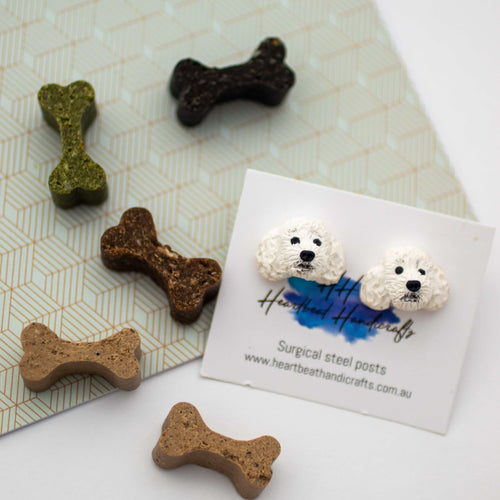 Handmade polymer clay white poodle stud earrings shown on surrounded by bone dog treats