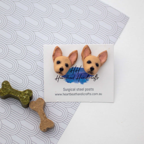 Handmade polymer clay chihuahua stud earrings displayed beside bone dog treats