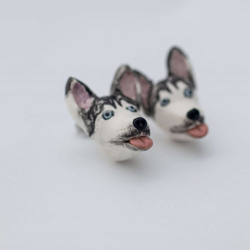 Handmade polymer clay husky stud earrings shown off cars up close