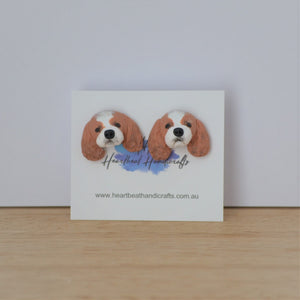 Handmade polymer clay Cavelier King Charles Spaniel stud earrings shown on timber
