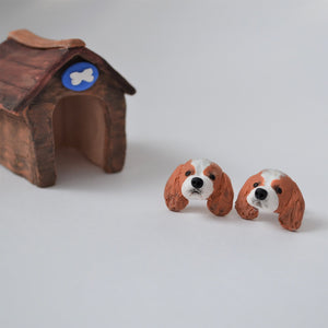 Handmade polymer clay Cavelier King Charles Spaniel stud earrings shown styled beside mini kennel