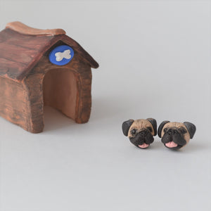Handmade polymer clay pug stud earrings shown styled in front of a mini kennel