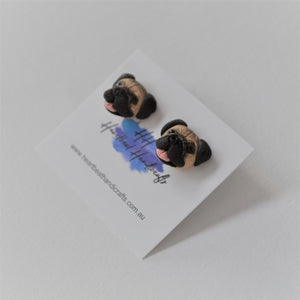 Handmade polymer clay pug stud earrings shown up close