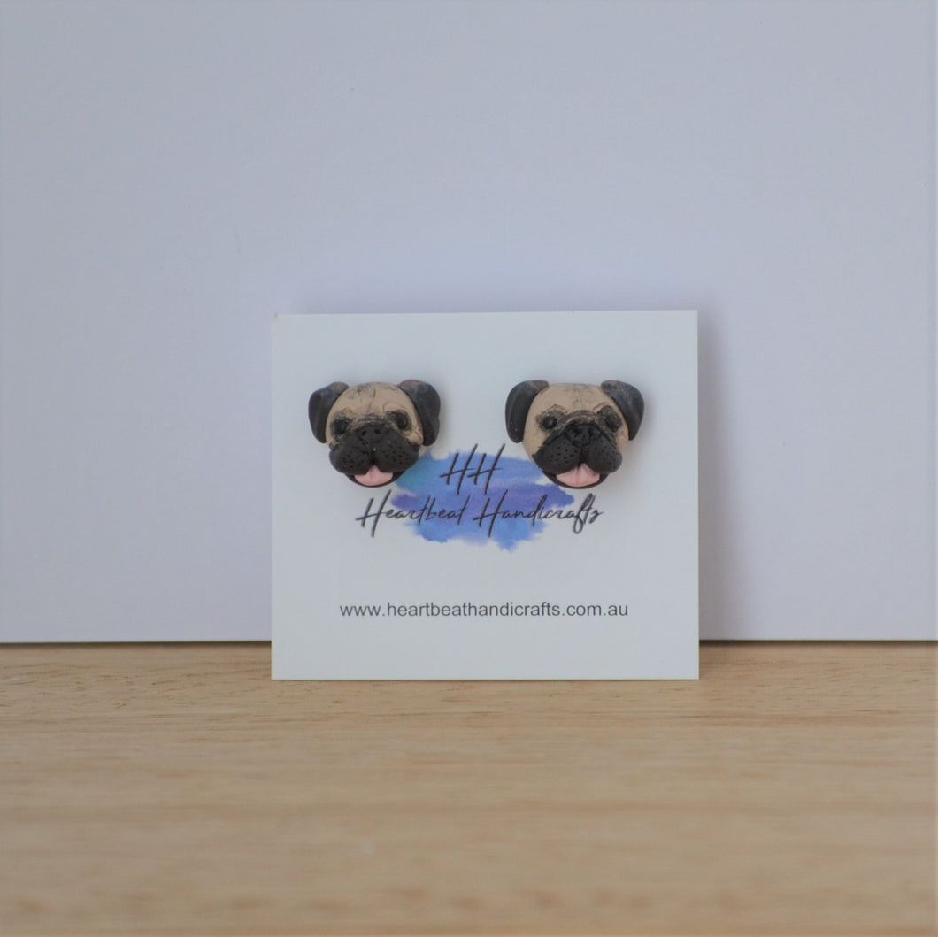 Handmade polymer clay pug stud earrings shown on timber