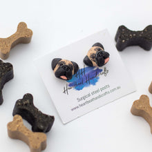 Handmade polymer clay pug stud earrings shown surrounded by bone dog treats