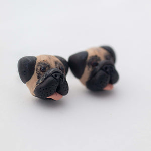 Handmade polymer clay pug stud earrings shown off card up close