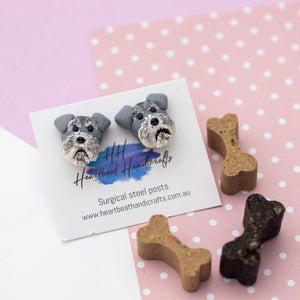 Handmade polymer clay schnauzer stud earrings surrounded by dog bone treats