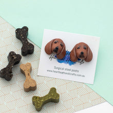 Handmade polymer clay Dachshund stud earrings shown on paper background surrounded by bone treats