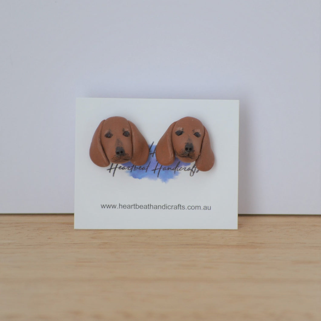 Handmade polymer clay Dachshund stud earrings shown on timber
