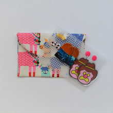 Cream with colourful llamas fabric handmade earrings travel pouch, pictured closed with several colourful sets of earrings on storage board displayed.
