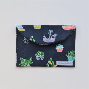 Navy and colourful pot plant fabric handmade earrings travel pouch, pictured closed.